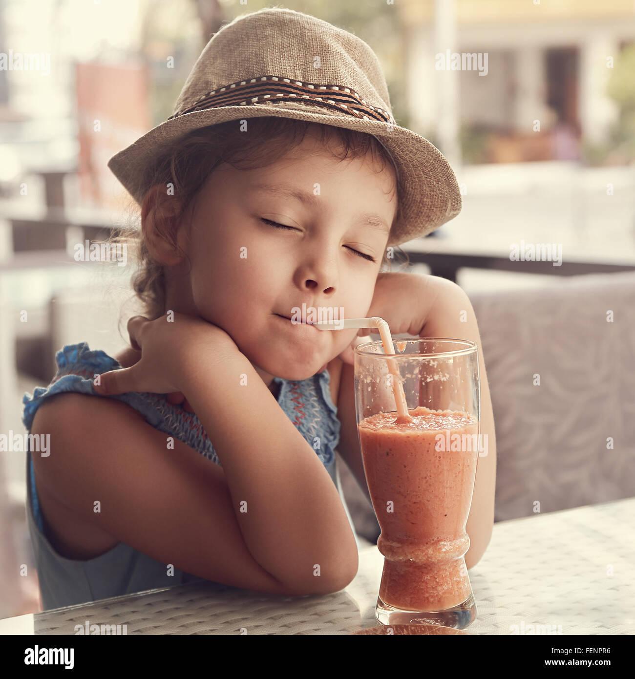 Heureux appréciant kid girl drinking smoothie délicieux jus naturel avec les yeux fermés dans le Photo Stock