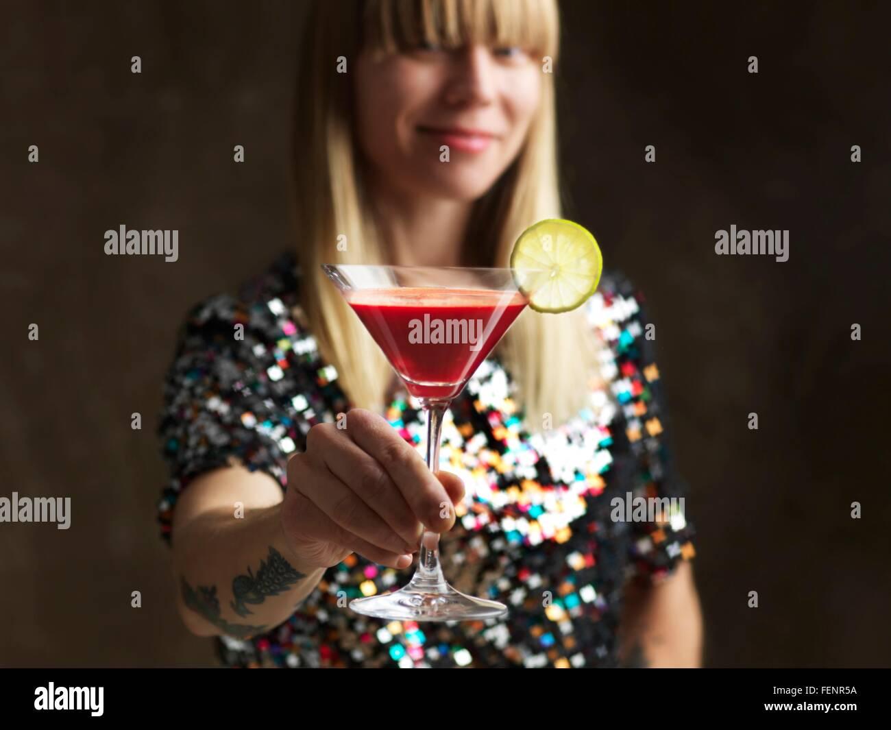 Mid adult woman holding jus cru dans verre à cocktail garni d'une tranche de lime smiling at camera Banque D'Images