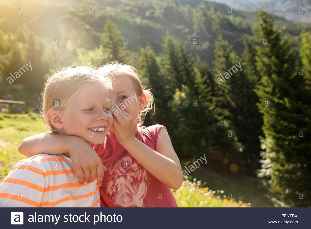 Jeune fille chuchoter dans l'oreille d'amis, à l'extérieur Photo Stock