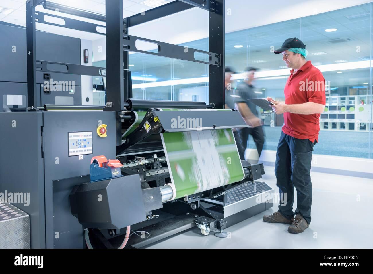 Travailleur avec imprimante à jet d'encre dans l'emballage alimentaire l'usine d'impression Photo Stock