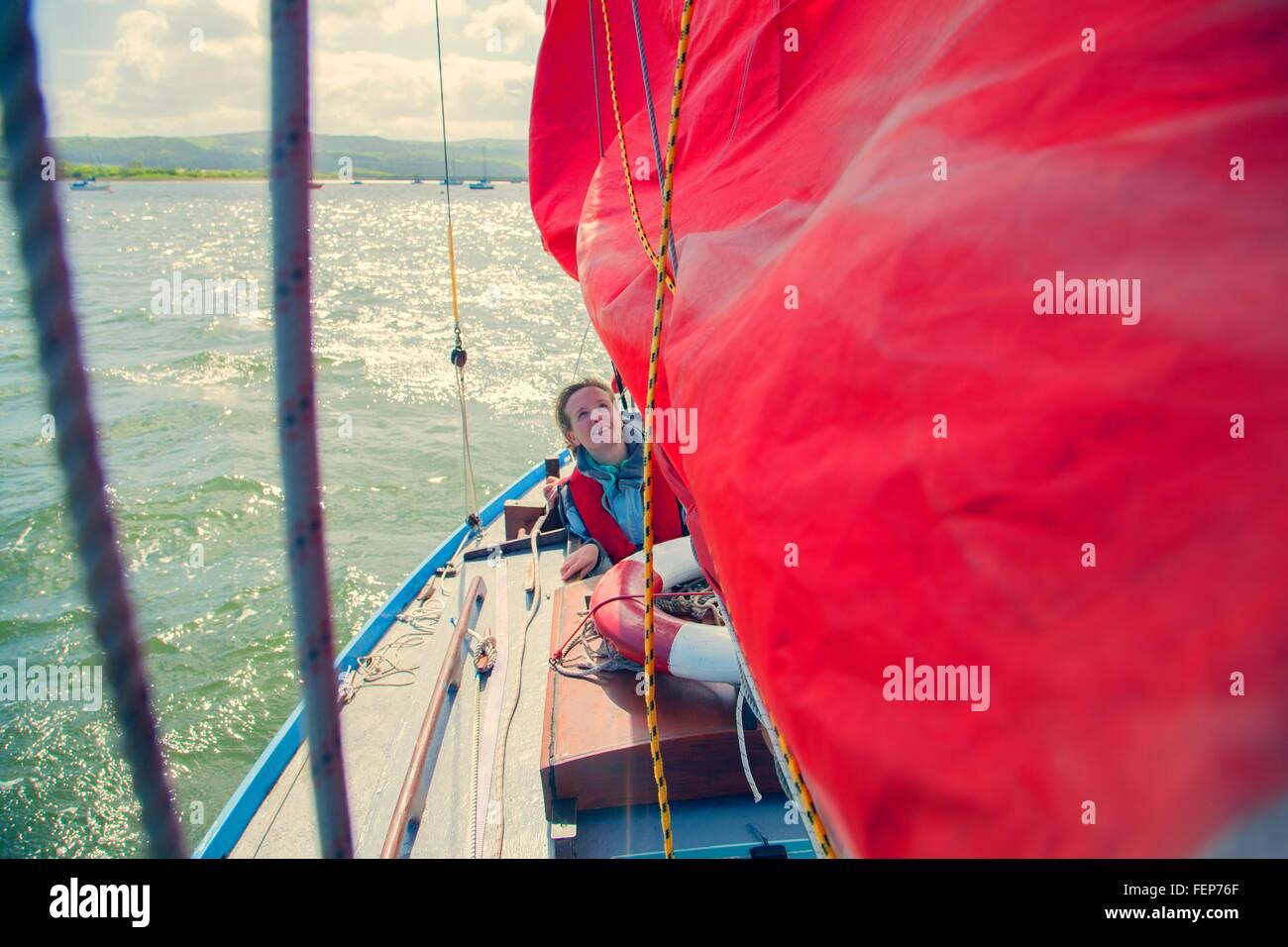 Mid adult woman sur bateau à voile Photo Stock