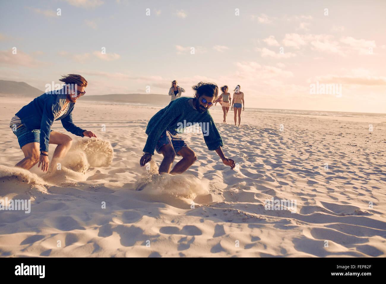 Les jeunes hommes course à pied sur la plage. Groupe de jeunes de jouer aux jeux de sable sur une journée Photo Stock