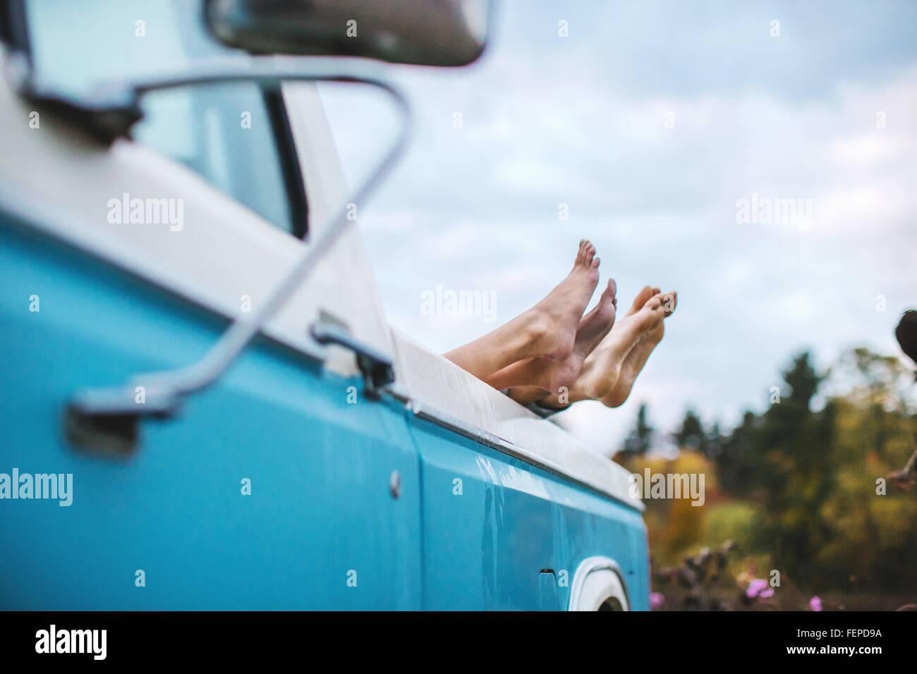 Jeune couple couché à l'arrière du camion, les pieds nus sur le bord du chariot, l'accent Photo Stock