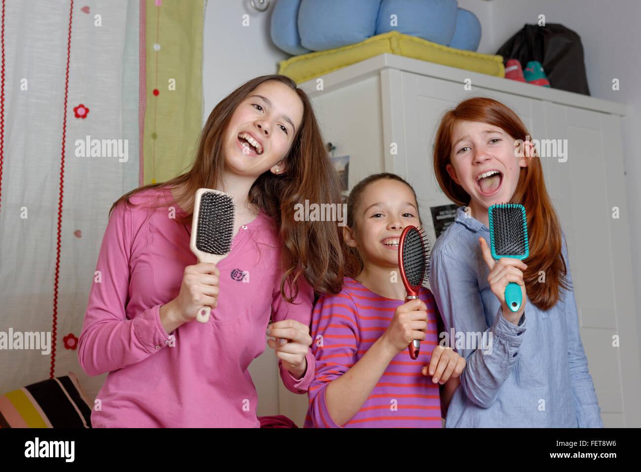 Les filles, les enfants chantent en brosse comme micro, Allemagne Photo Stock