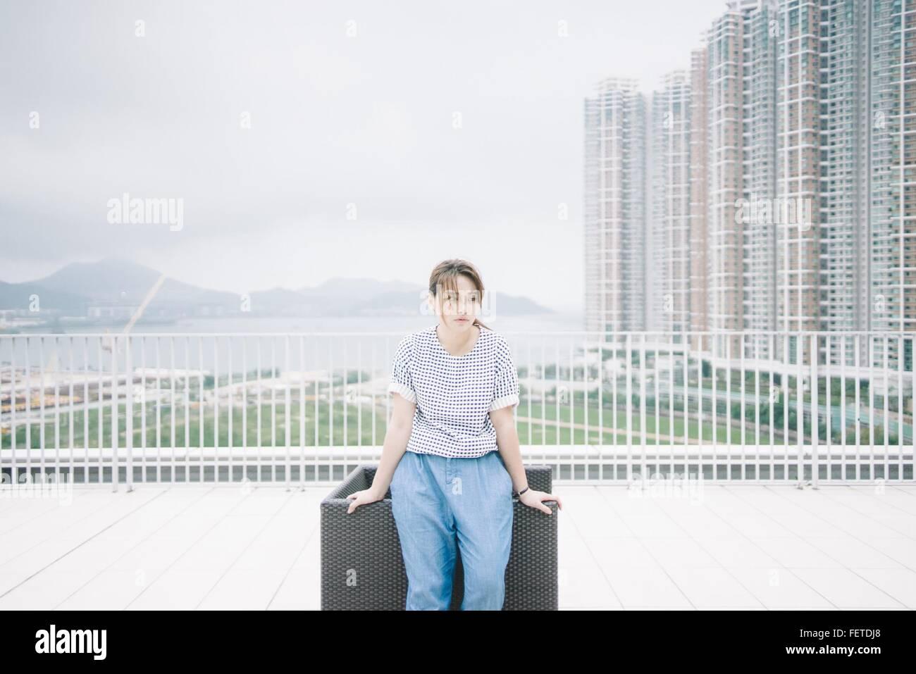 Thoughtful Woman Leaning par chaise contre des immeubles modernes Photo Stock