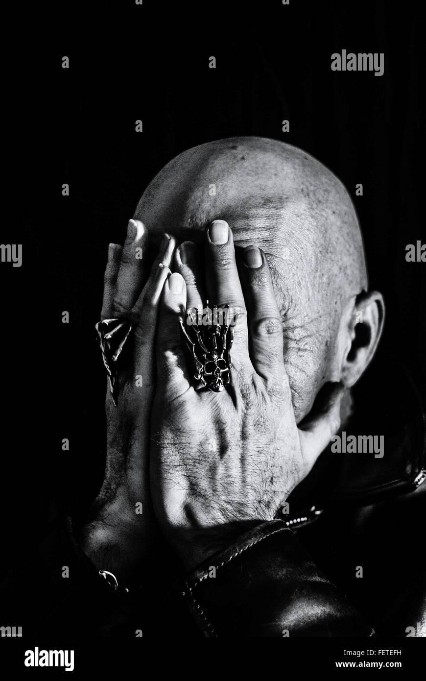 Homme chauve couvrant le visage avec les mains Photo Stock