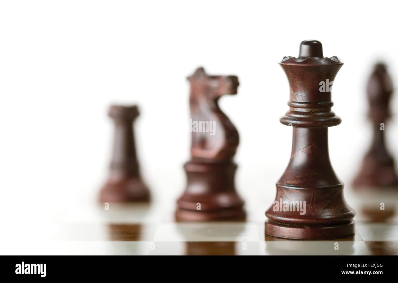 Image horizontale d'une partie d'échecs avec l'accent sur la reine et un flou des pièces de plus de fond blanc, copie de l'espace sur le côté gauche. Banque D'Images