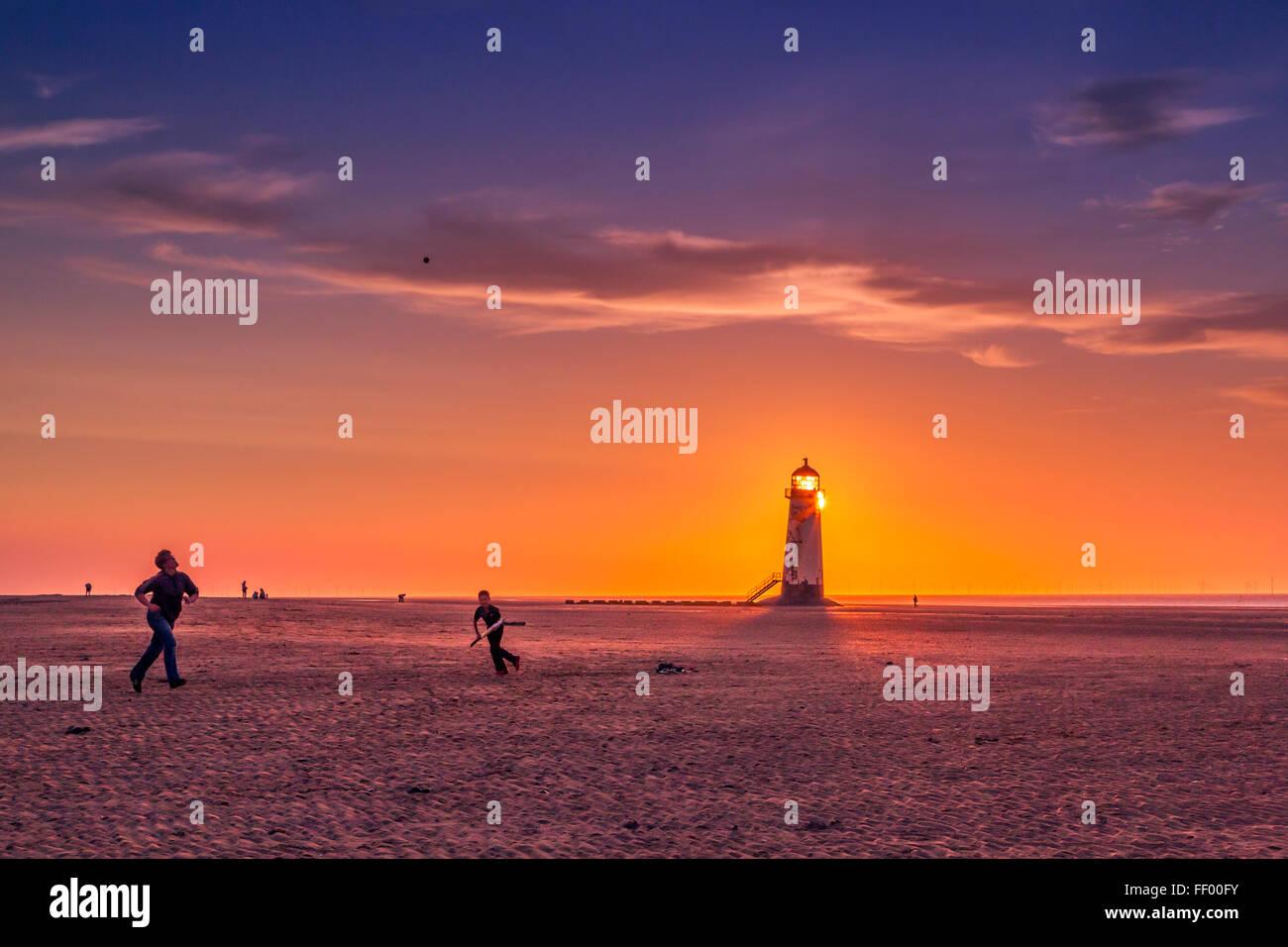 Jouer beach cricket sur plage de Talacre au coucher du soleil. Photo Stock
