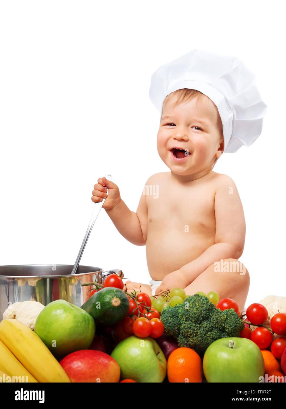 Baby Boy in chef hat avec plat de cuisson et les légumes Photo Stock