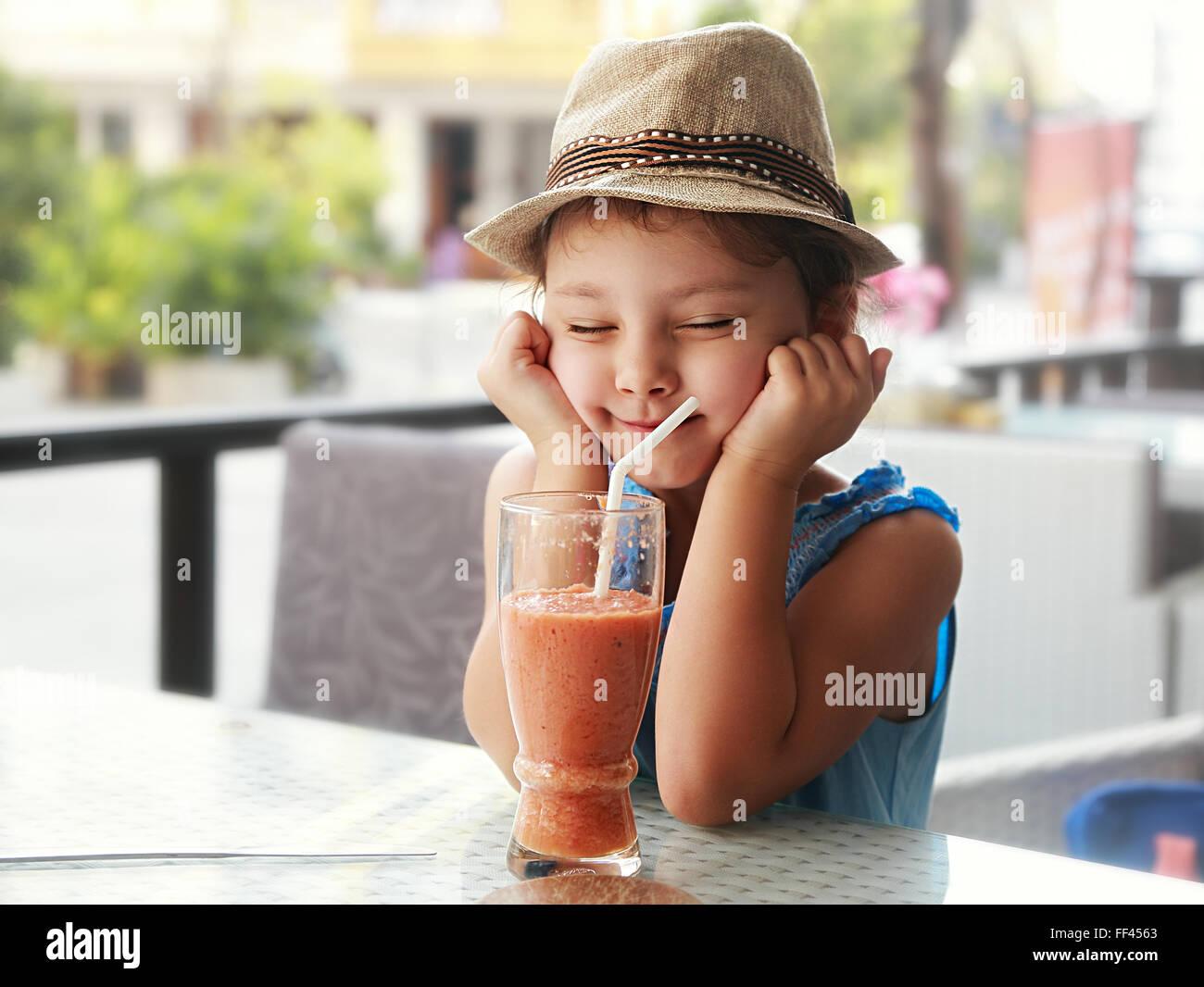 Fun kid girl hat en vissant les yeux et attend le moment pour boire le jus délicieux smoothie sur fond d'été Photo Stock