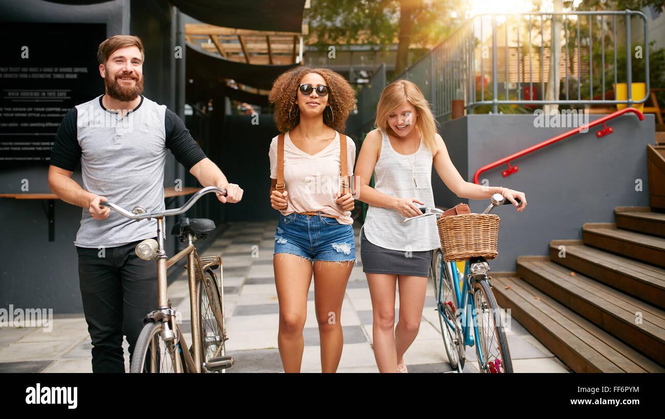 Trois jeunes gens marchant dans la rue avec leur vélo. Les amis masculins et féminins sur route avec leur Photo Stock