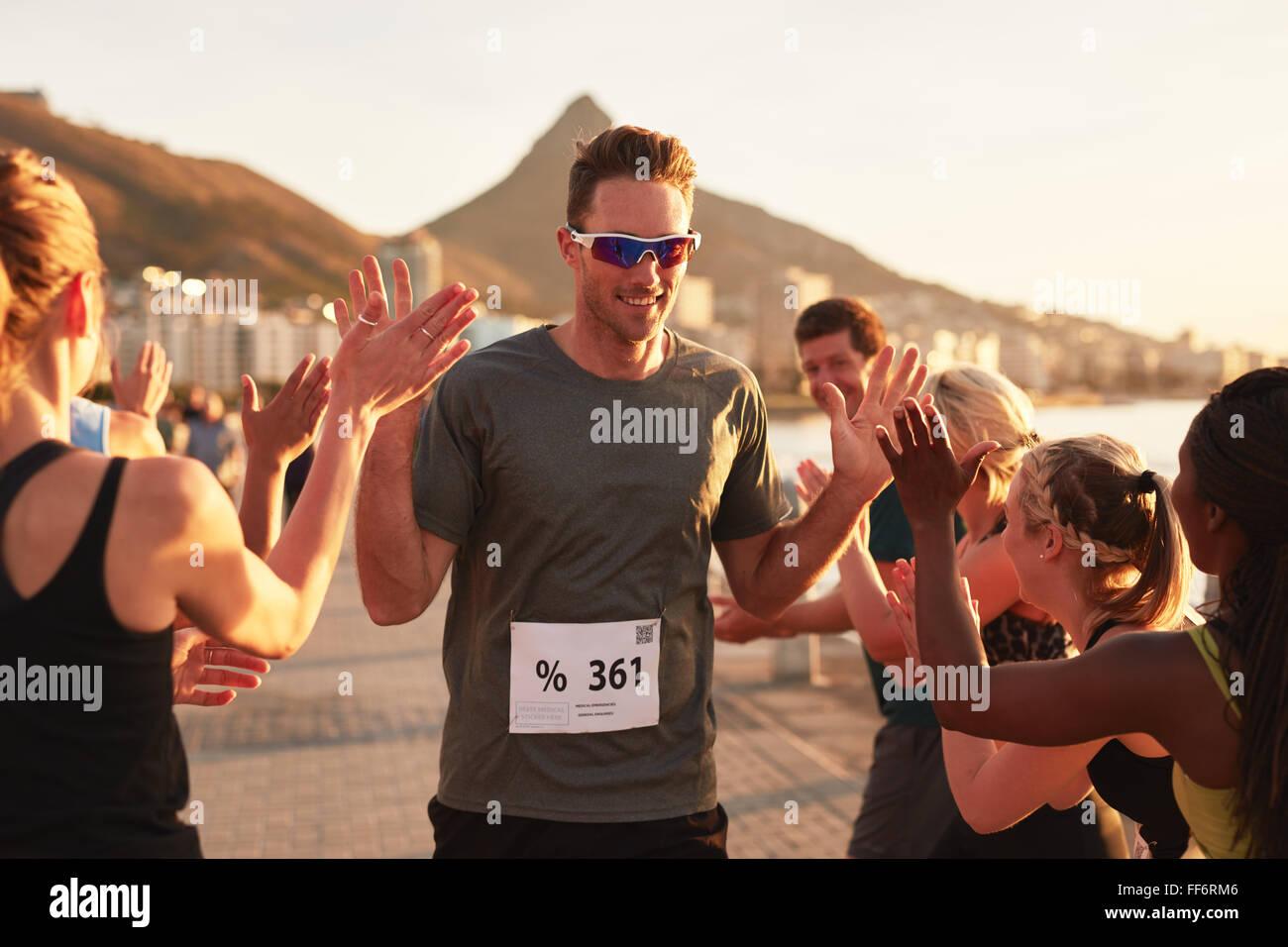 Groupe de jeunes adultes et d'encourager un athlète masculin fiving haut traversant la ligne d'arrivée. Photo Stock