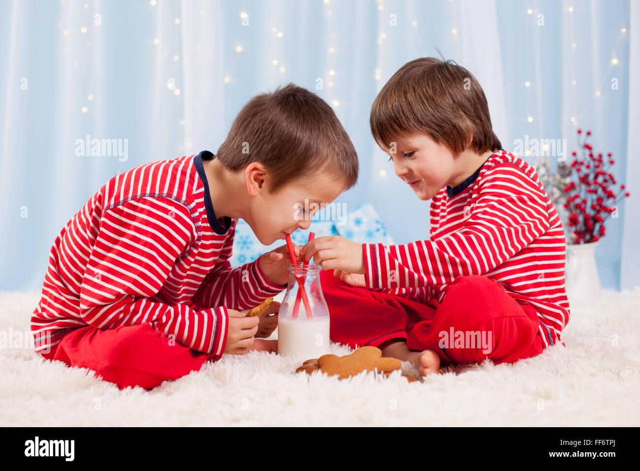 Deux enfants heureux de manger des biscuits de Noël et boire du lait, de rire et de parler, s'amuser Photo Stock