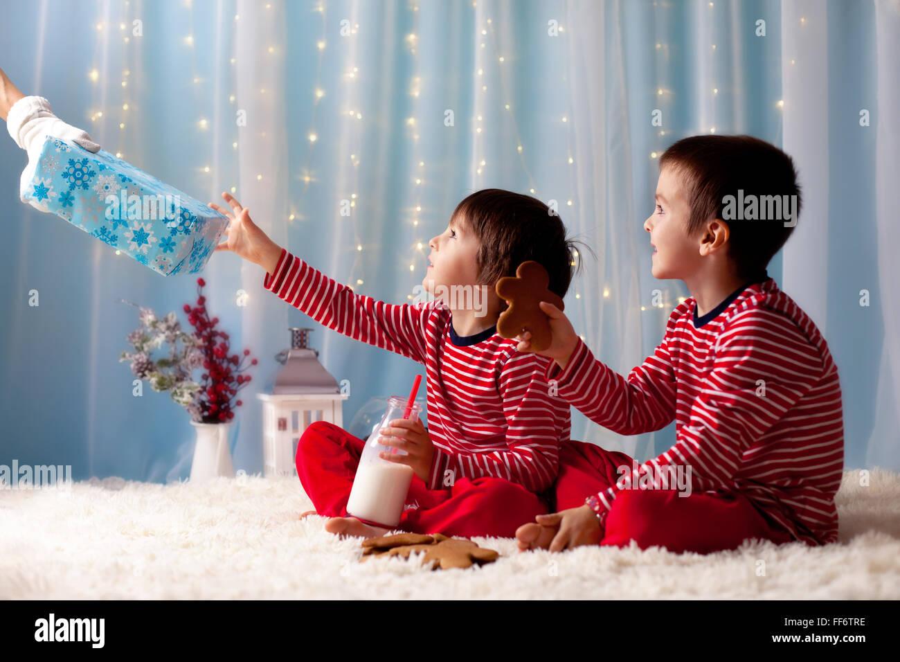 Deux petits garçons en pyjama, l'attente du Père Noël, Santa les présente, pour les enfants Photo Stock
