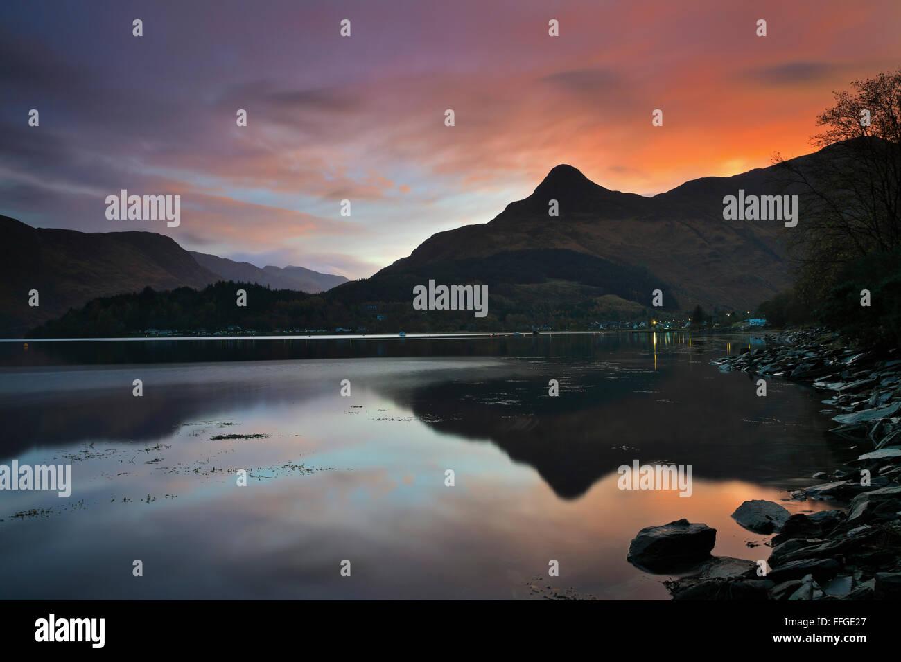 Le Pap of Glencoe dans les Highlands écossais, reflétée dans le Loch Leven au lever du soleil au Photo Stock