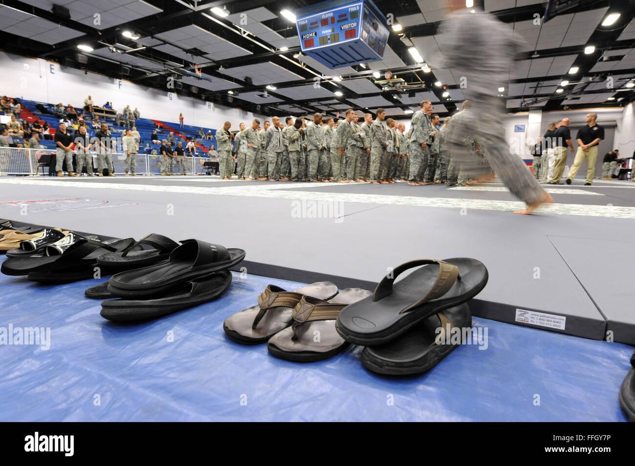 Un membre de service passe devant une ligne de sandales à rejoindre les autres concurrents en formation au Photo Stock