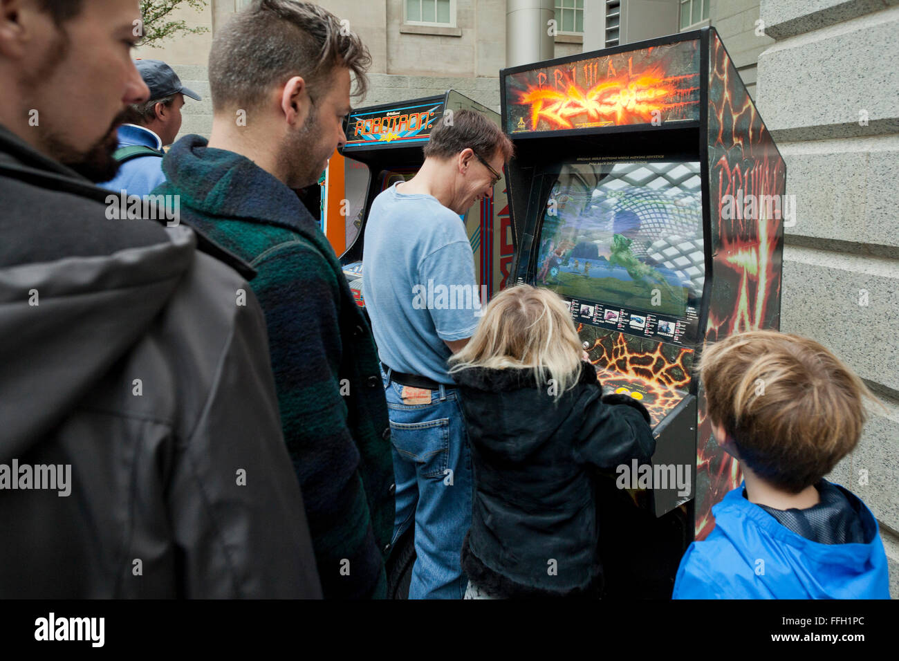 Man playing video game arcade avec fille - USA Photo Stock