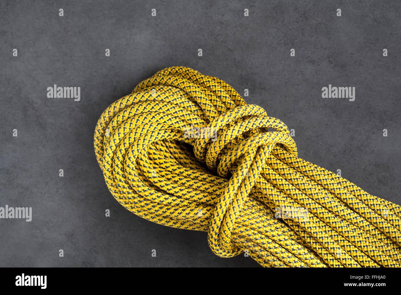 Corde dynamique d'escalade jaune sur fond sombre Photo Stock