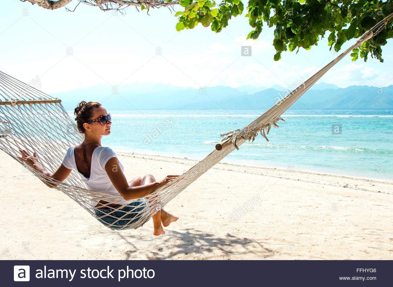 Girl relaxing in hammock sur la plage près de l'océan bleu. Bali, Indonésie. Le point de droit. Banque D'Images