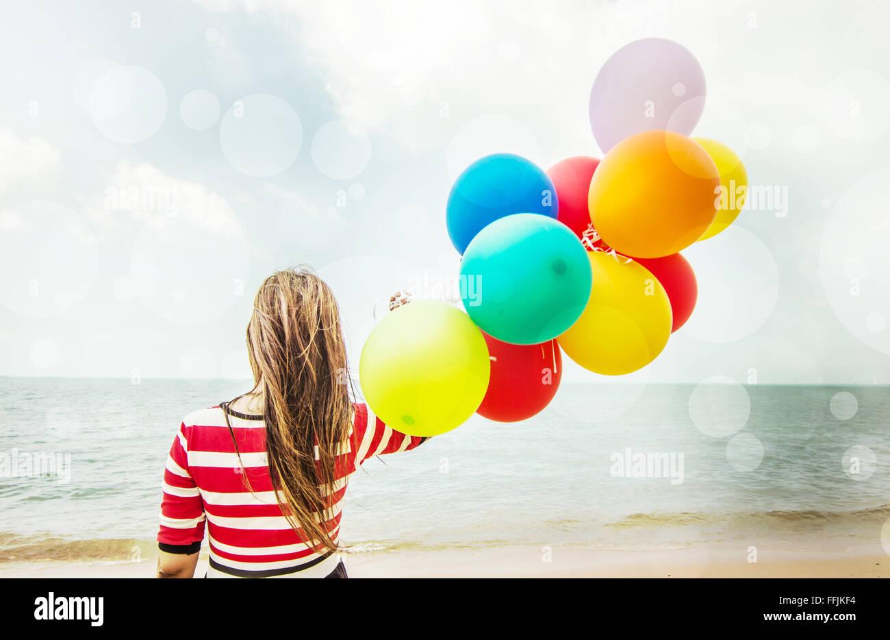 Femme avec des ballons colorés sur la plage, à l'extérieur de l'image Filtres de vieBanque D'Images