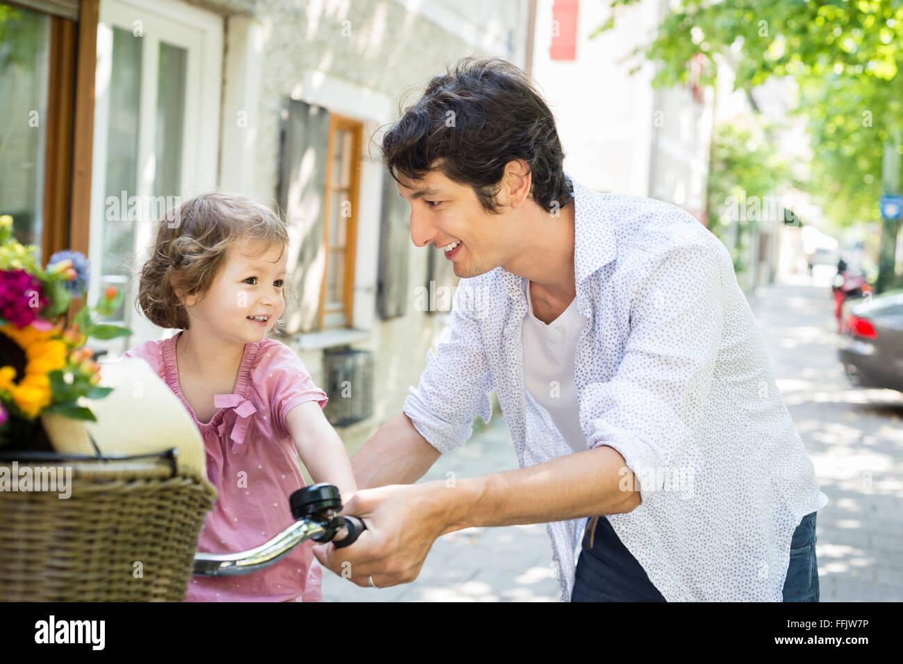 Père et fille poussant ensemble vélo Photo Stock
