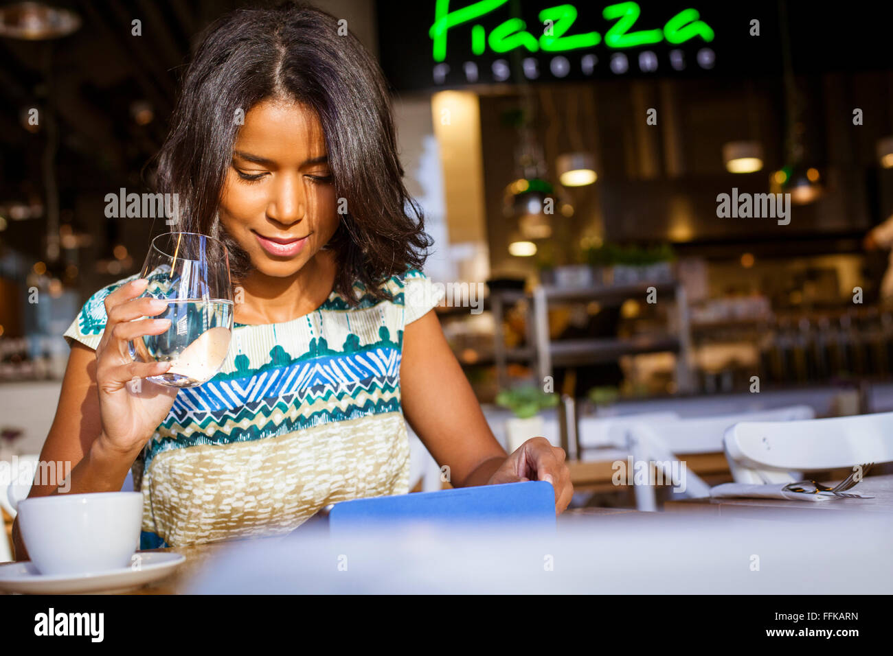Mixed Race woman se trouve dans cafe en utilisant ordinateur Photo Stock
