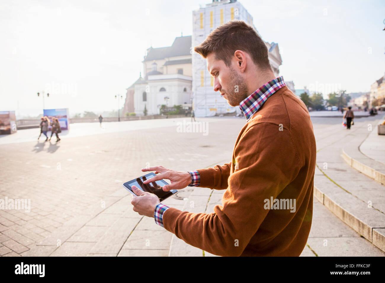 L'homme sur un séjour en ville à l'aide d'un écran tactile Photo Stock