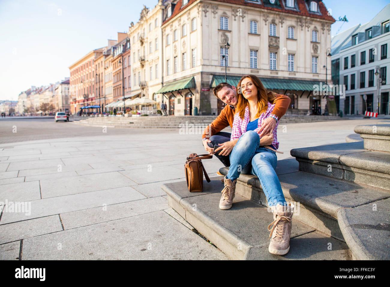 Couple sur un séjour en ville reposant sur town square Photo Stock