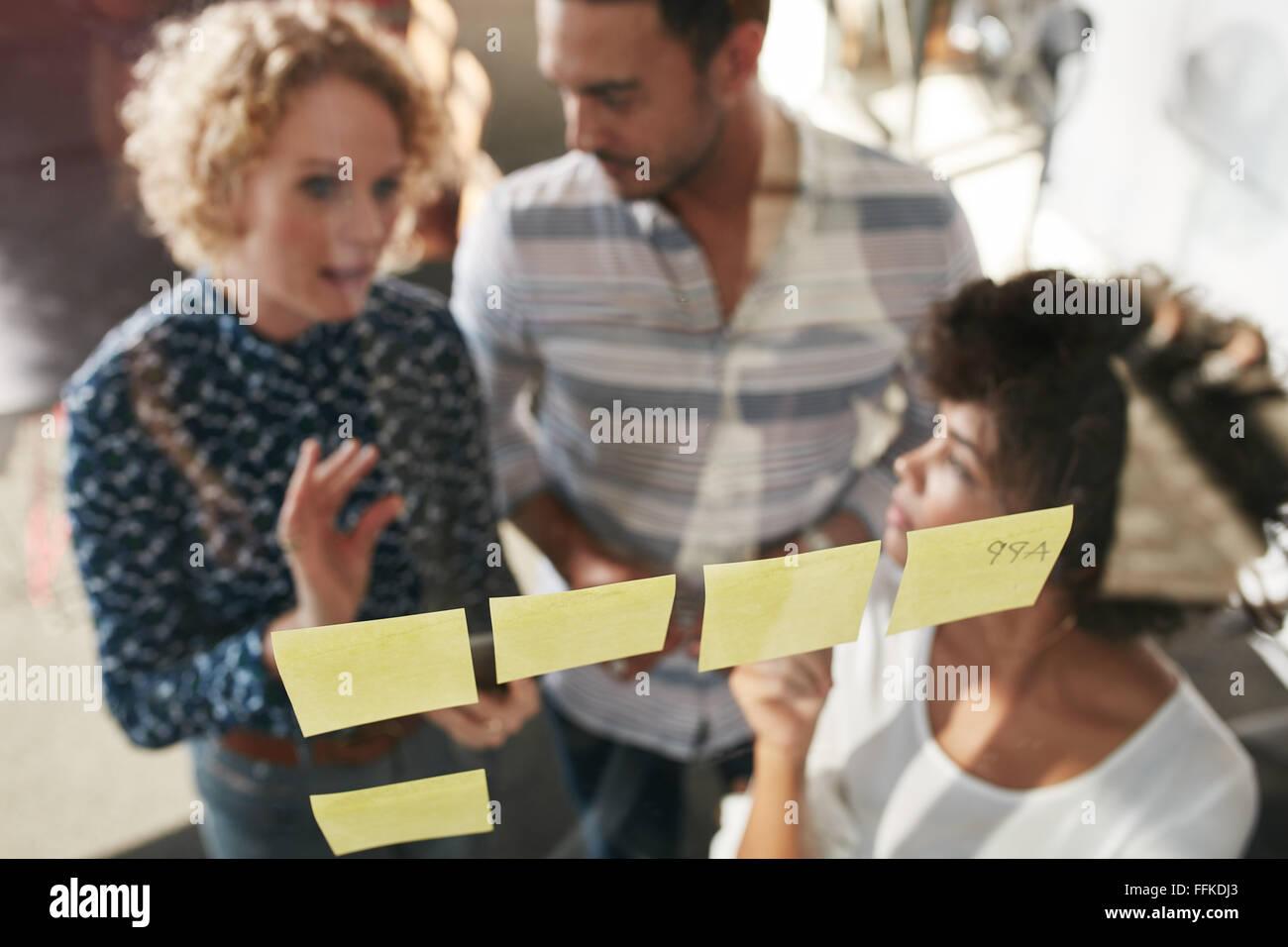 Trois personnes ayant une réunion de bureau. Ils sont debout en face de paroi en verre avec post it et de discussions. Photo Stock