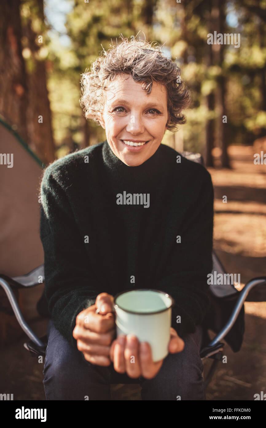 Portrait of senior woman sitting en dehors de la tente avec une tasse de café. Les femmes de race blanche tenant Photo Stock