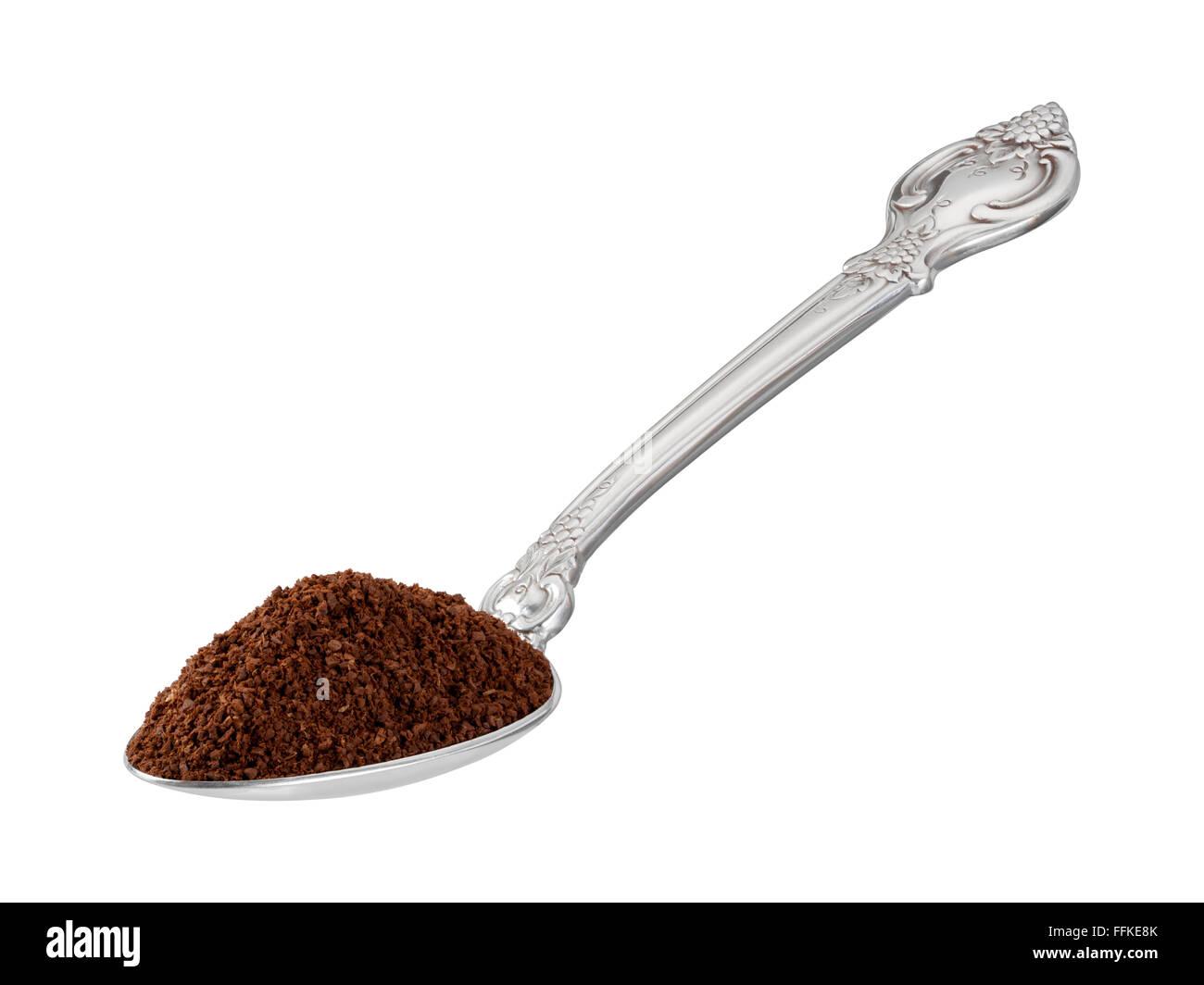 Scoop du café moulu dans une cuillère. L'image est un coupé, isolé sur un fond blanc. Photo Stock