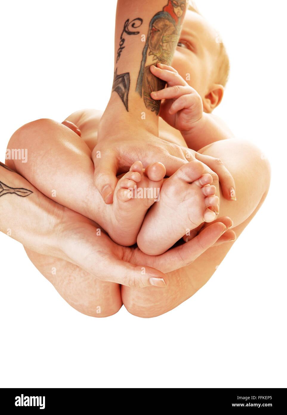 Une Jeune Mere En Tatouage Sur Ses Bras Tenant Les Pieds De Son Bebe