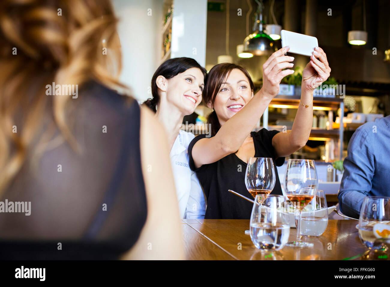 Deux femmes prenant un restaurant en selfies Photo Stock