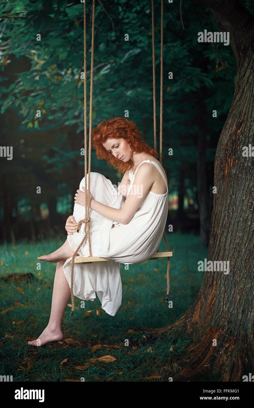 Belle femme réfléchie sur une balançoire dans le bois . Portrait romantique et vintage Photo Stock