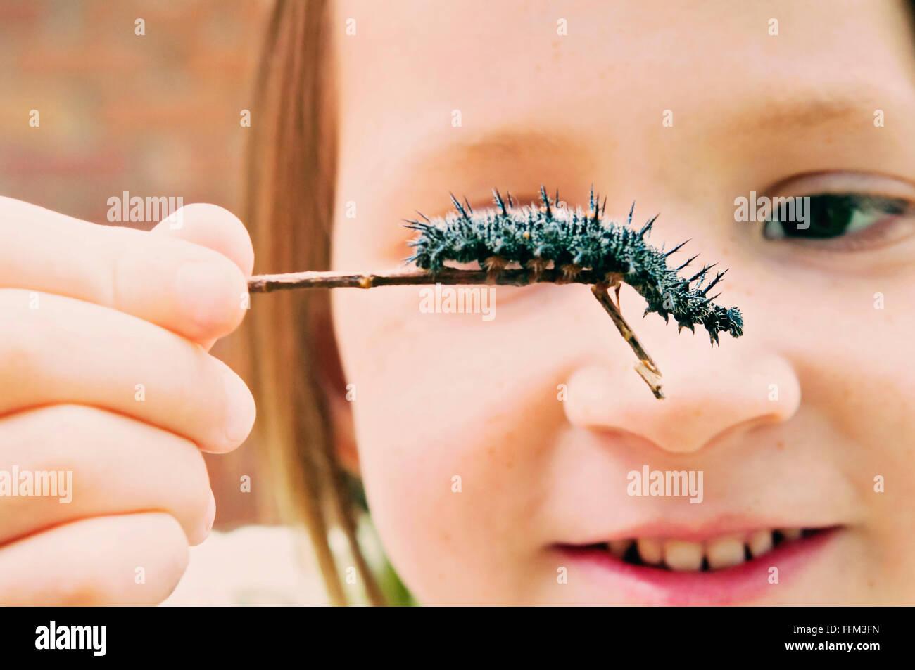 Girl holding peacock Caterpillar Photo Stock