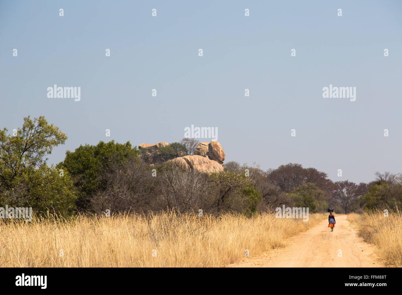 Une femme avec un ensemble en équilibre sur sa tête marchant dans un chemin de terre rurale dans l'ouest Photo Stock