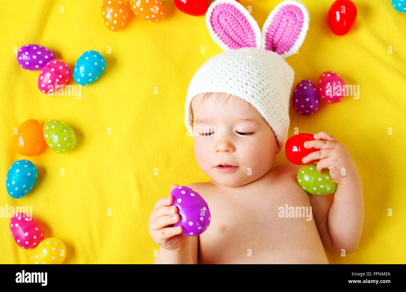 Baby Boy in bunny hat lying on couverture jaune avec des oeufs de pâques Photo Stock