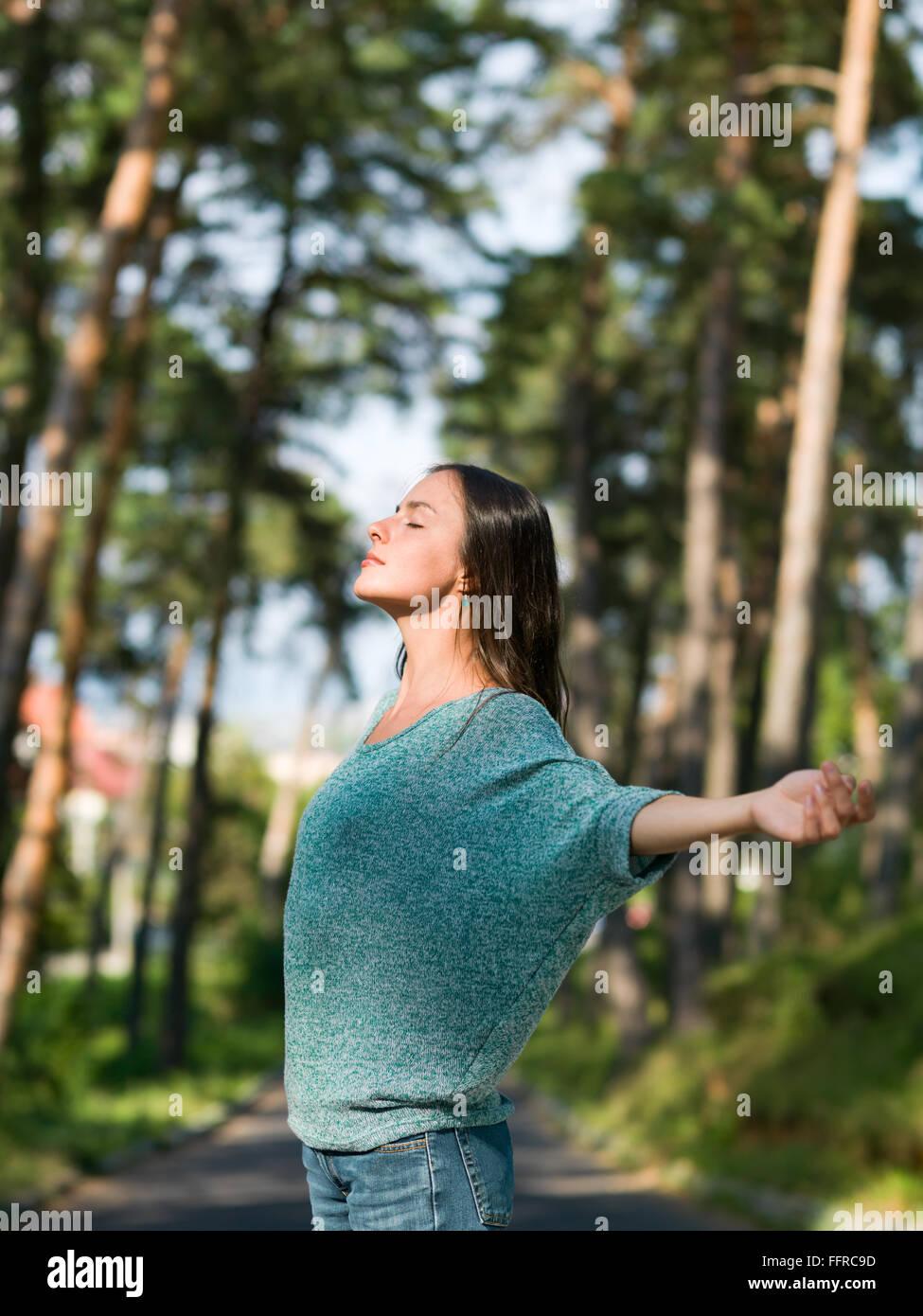 Belle jeune femme profitant du beau temps dans une allée avec des arbres verts Photo Stock