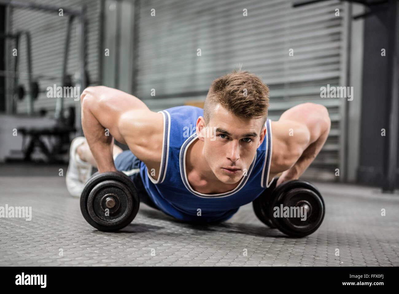 L'homme musclé faisant push up with dumbbells Banque D'Images