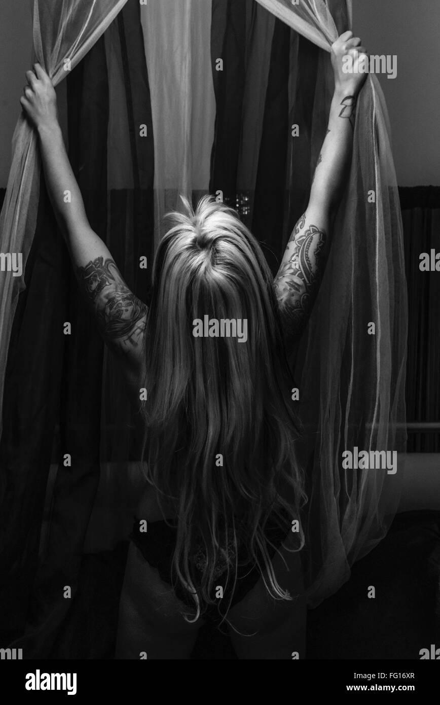Vue arrière du rideau de la fenêtre d'ouverture de la femme Photo Stock