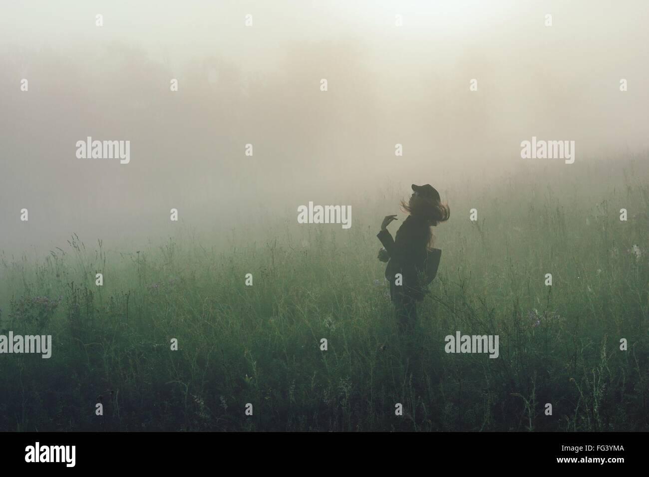 Femme debout sur les champs pendant temps de brouillard Photo Stock