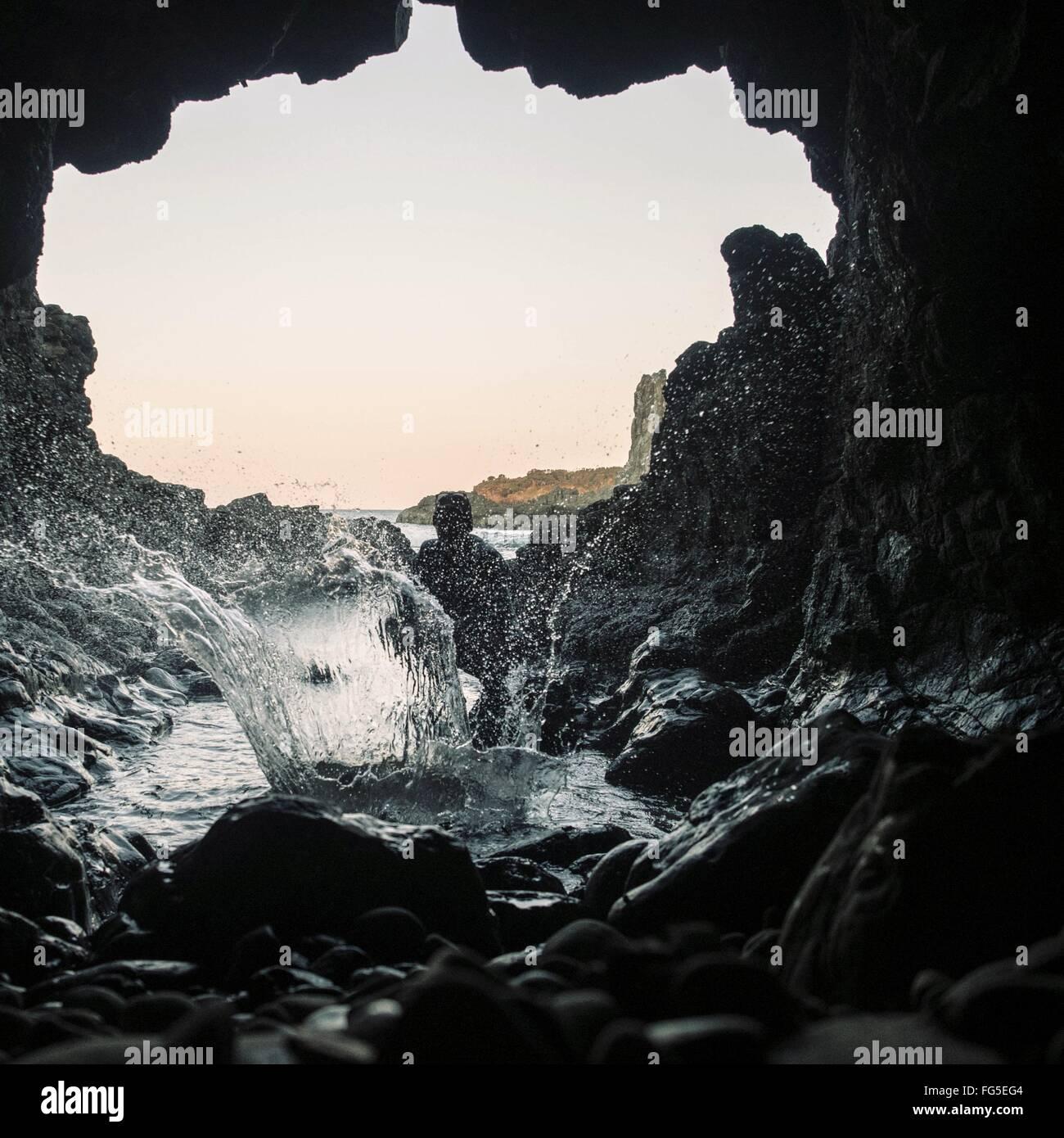 Personne aux projections d'eau en dessous de la rivière Rock Formation contre Ciel clair Photo Stock