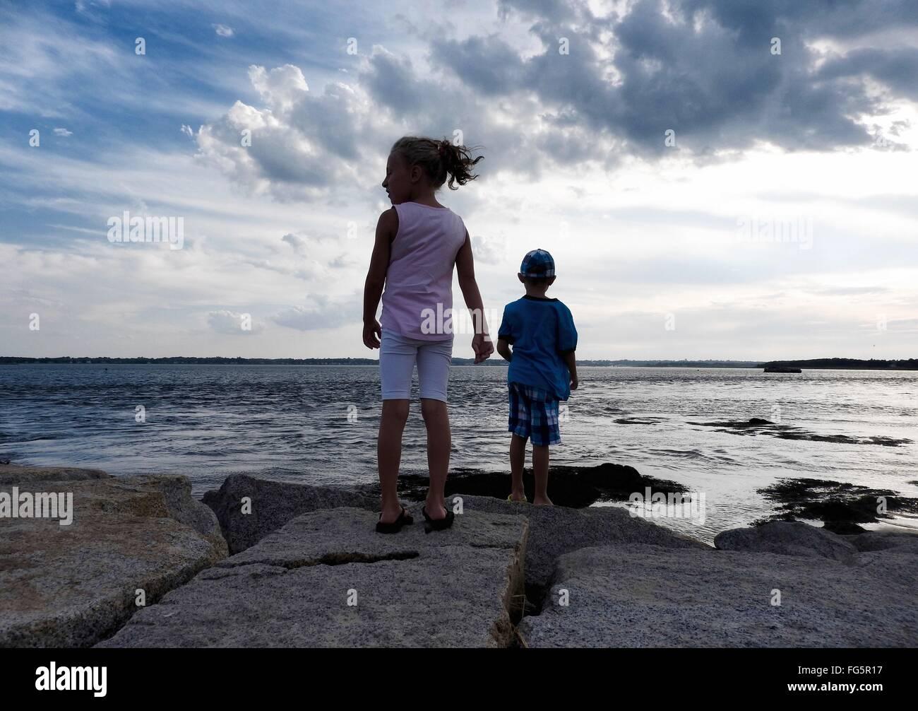Vue arrière de la fratrie debout sur des rochers au bord de mer contre Ciel nuageux Photo Stock
