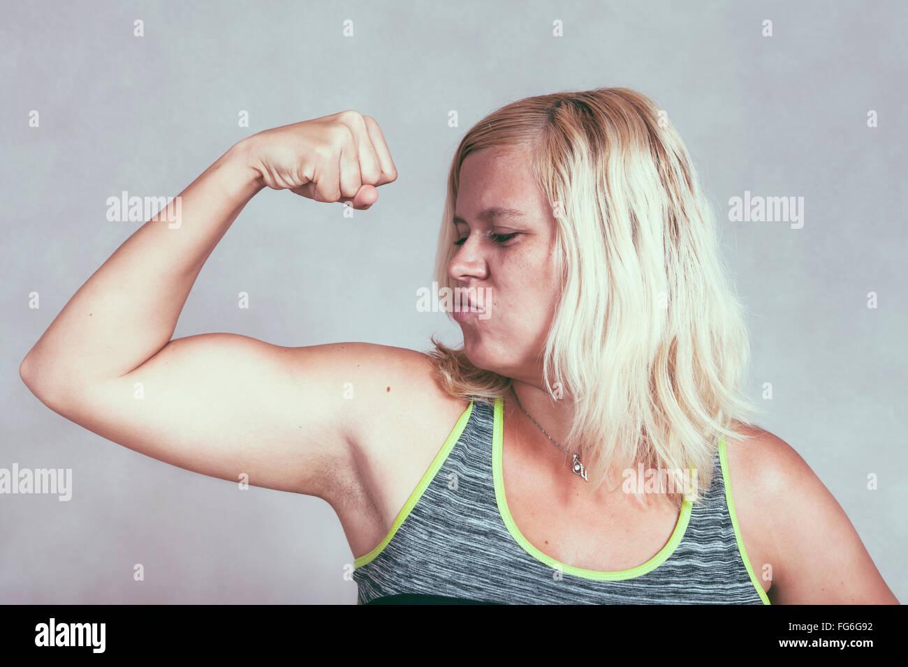 Une forte confiance woman flexing musculaire des muscles. Jeune femme sportive blonde montrant le bras et des biceps. Photo Stock