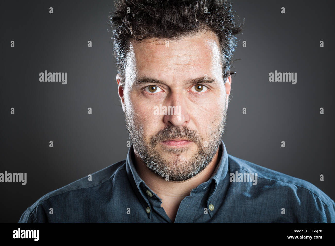 Portrait of Serious Man Standing Against Gray Background Photo Stock