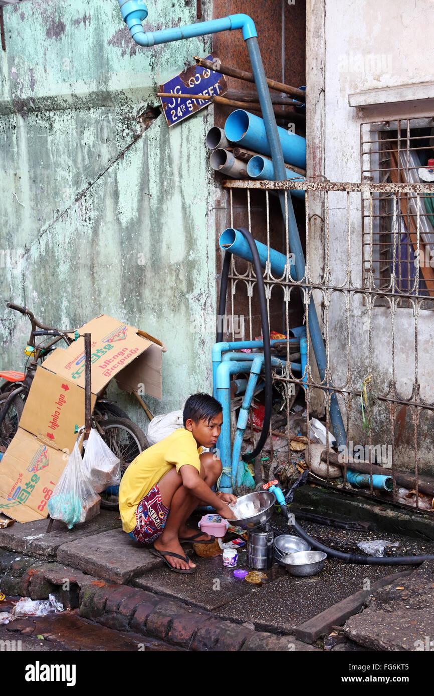 Garçon laver la vaisselle dans la Rue, Yangon, Myanmar Banque D'Images