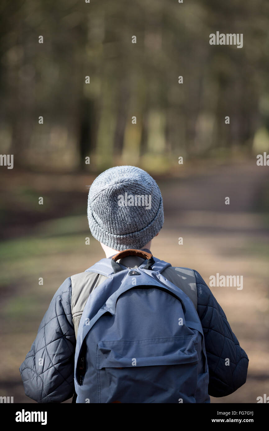 Un garçon avec un sac à dos randonnée dans les bois Photo Stock