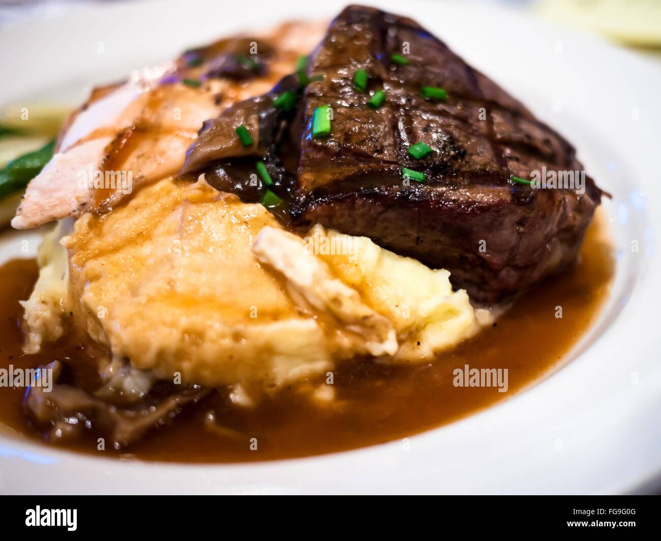 Steak, pommes de terre, et de la sauce sur une assiette blanche Photo Stock