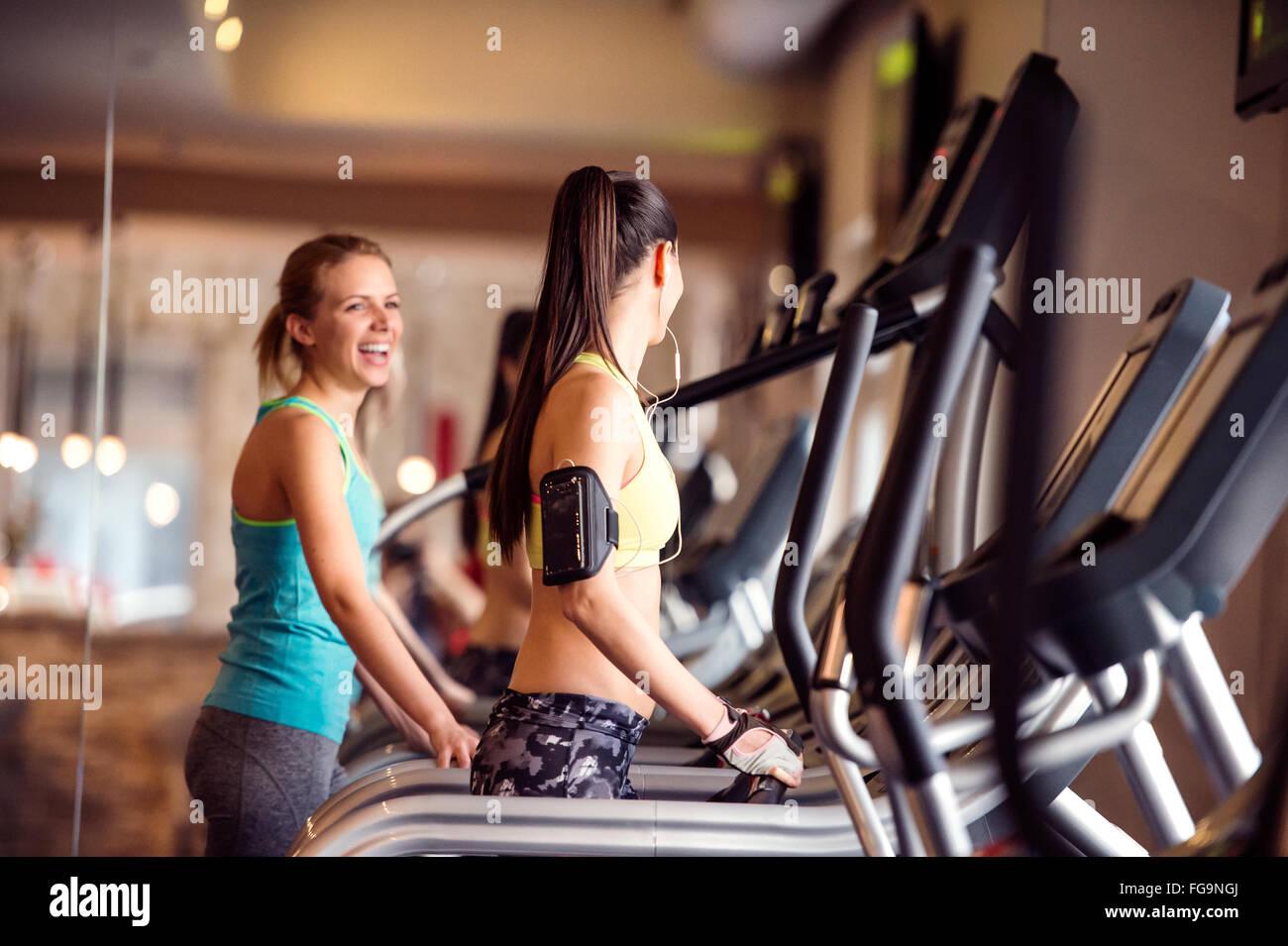 Deux femmes s'exécutant sur des tapis roulants dans la salle de sport moderne Photo Stock