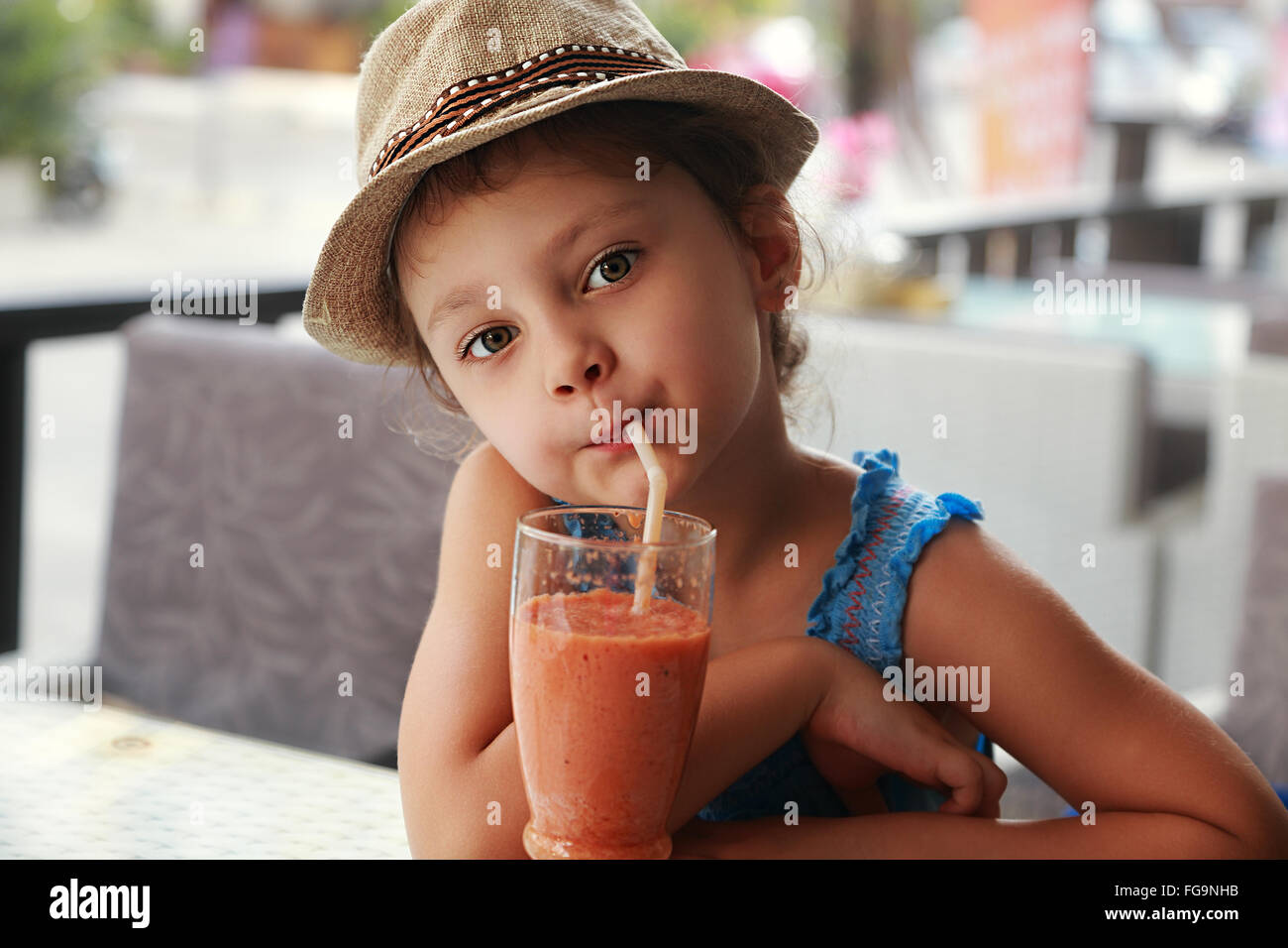 Fun kid cute girl drinking smoothie sain jus dans street restaurant. Closeup portrait Photo Stock